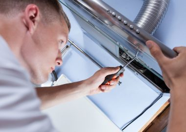 Young handyman fixing a kitchen extractor with a screwdriver